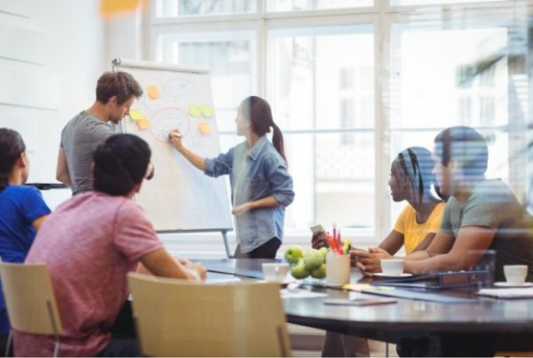 business-executives-discussing-with-their-colleagues-whiteboard